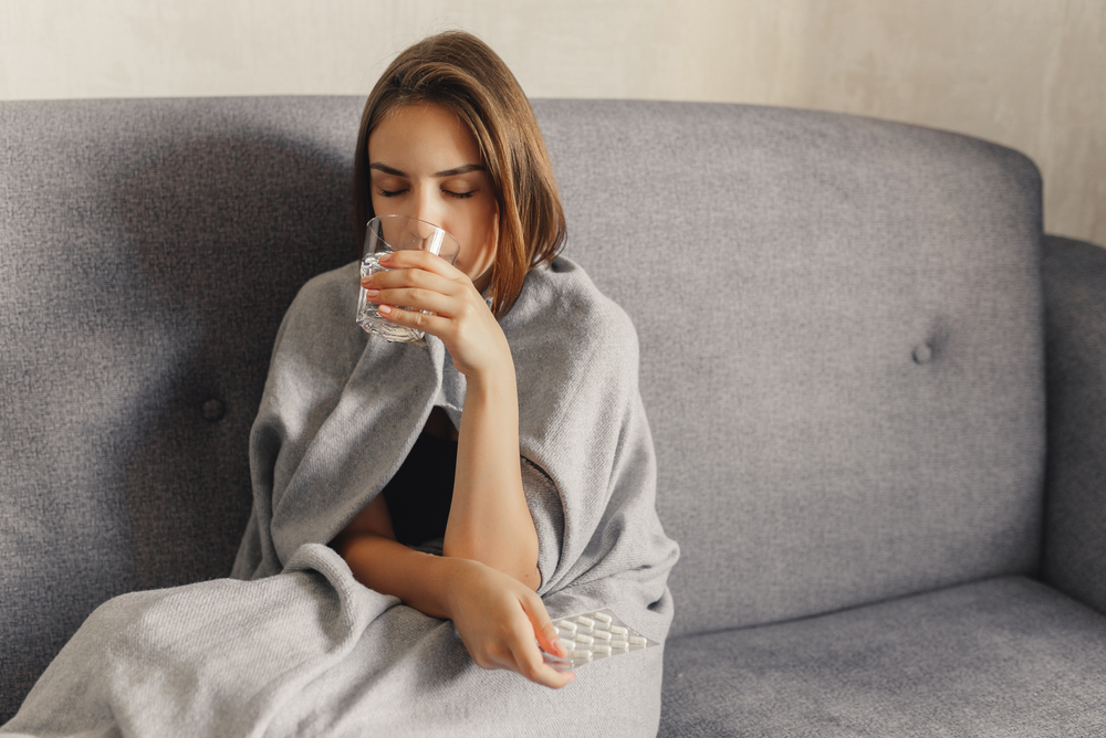 sick woman drinking water on couch