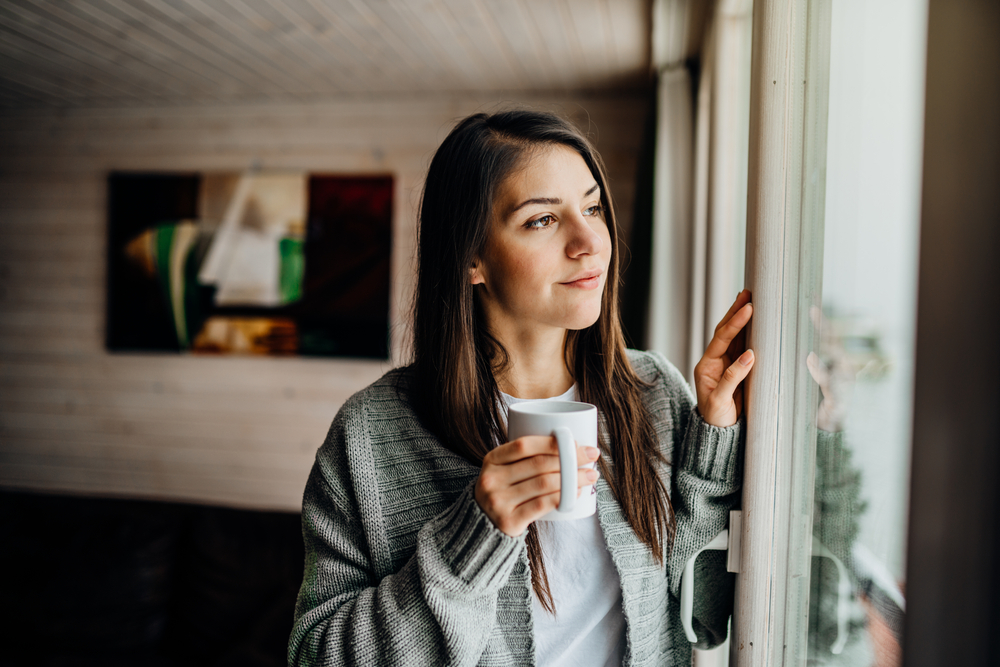 smiling woman looking out window with tea
