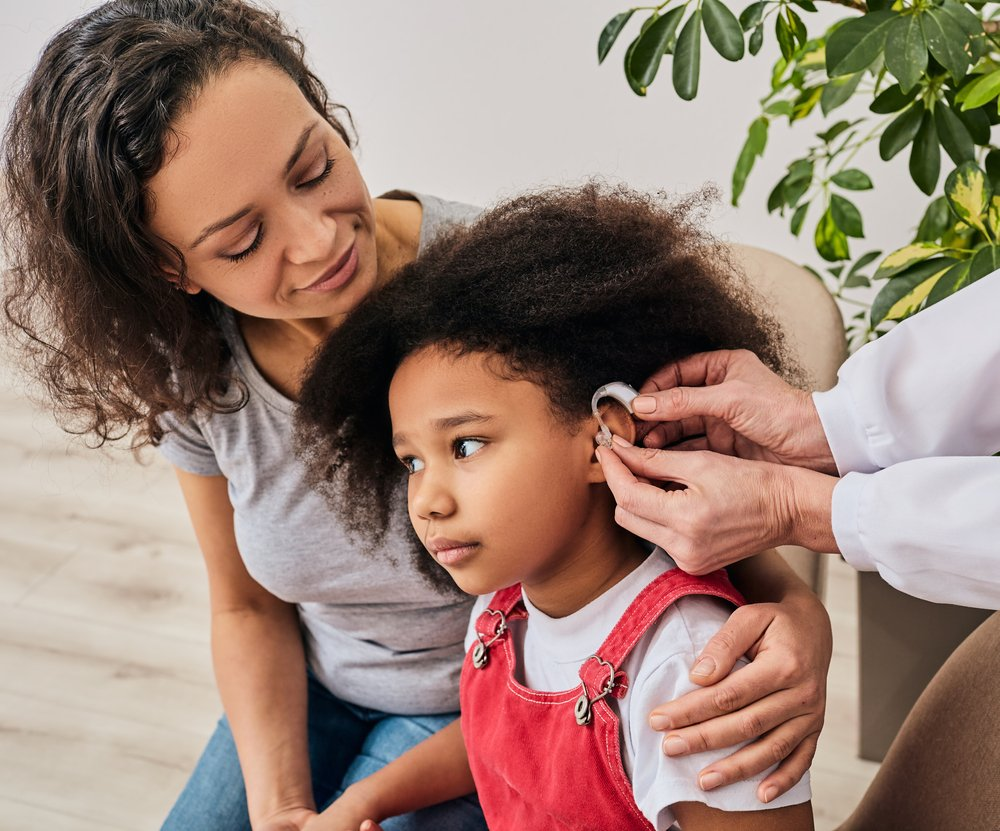 little girl being fitted for a hearing aid, with mother