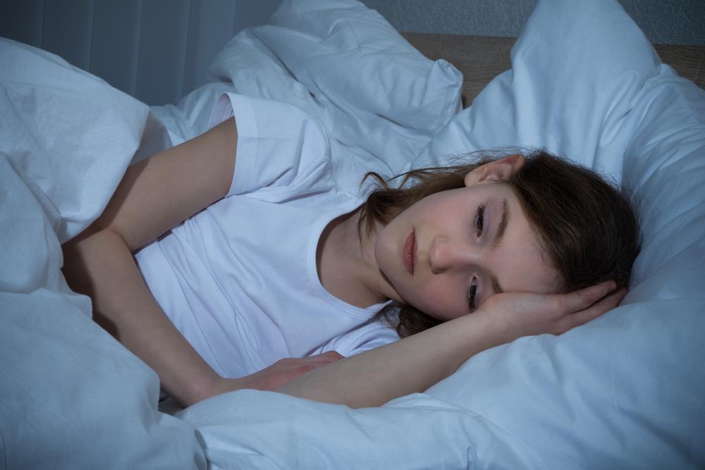 little girl lying awake in bed