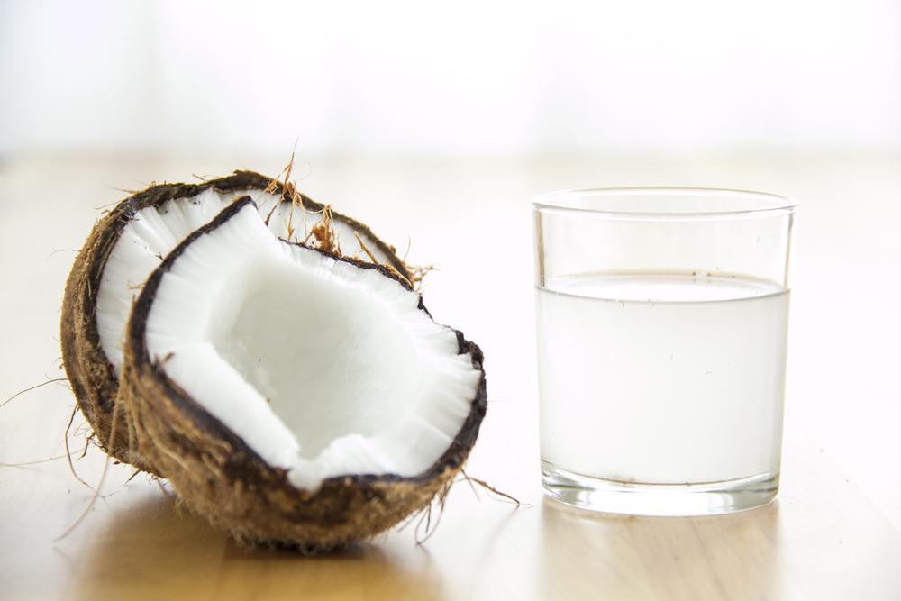 fresh coconuts sitting beside glass of coconut vinegar