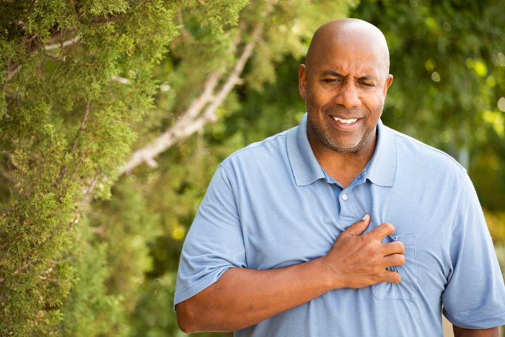middle aged man walking outside grasping chest