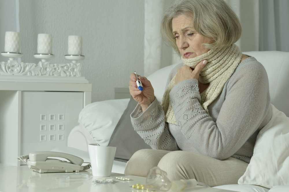 sick woman checking temperature with thermometer