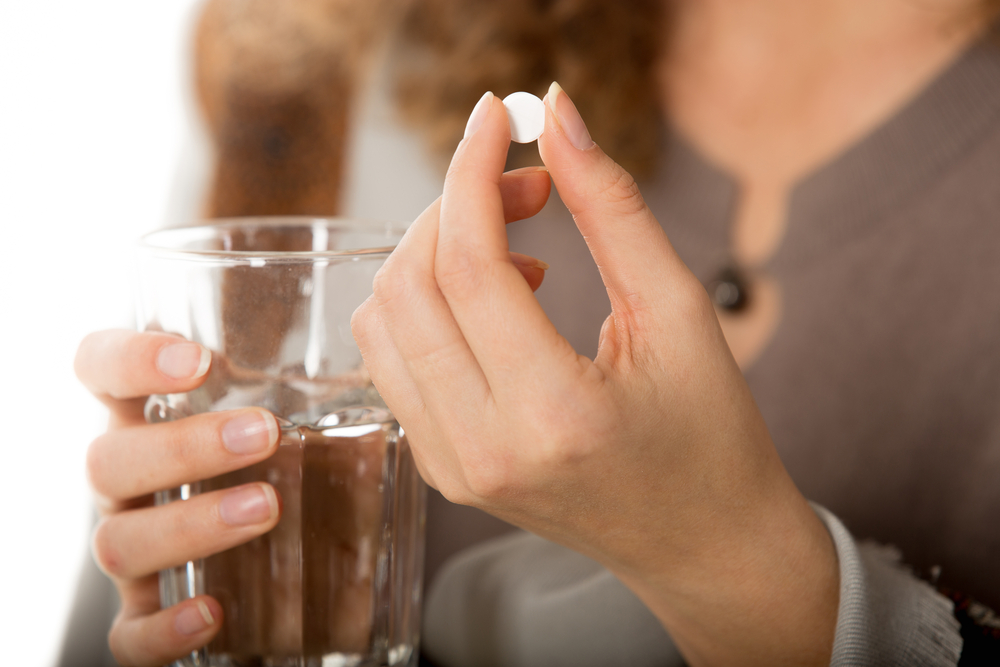 close up of woman taking pill with water