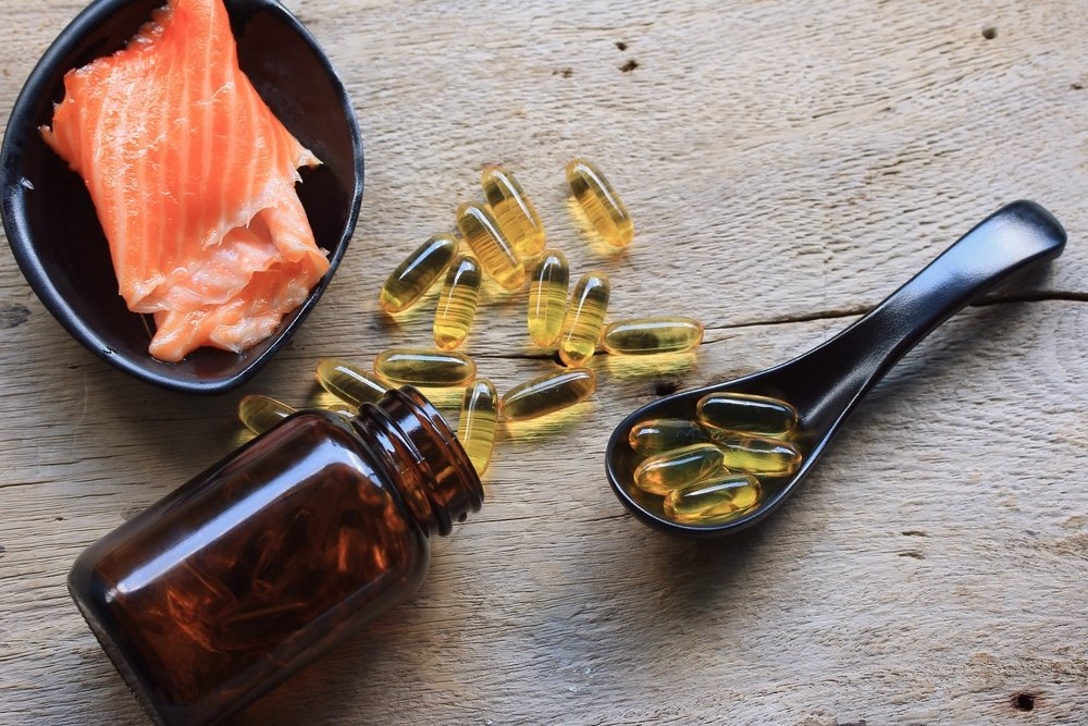 fish oil concept with capsules and raw salmon