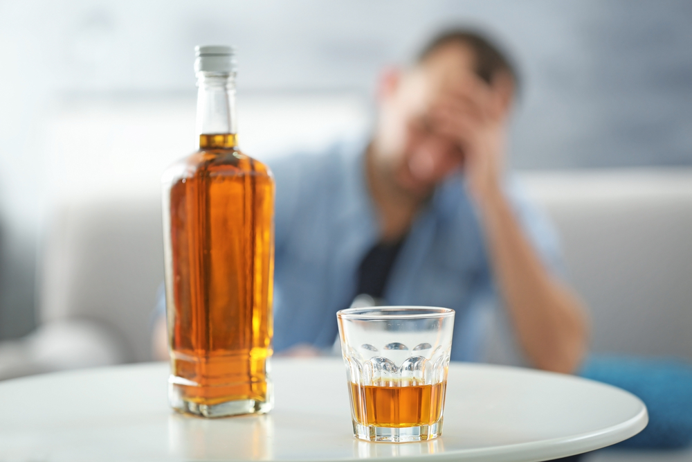 alcohol bottle in foreground, sad man in background