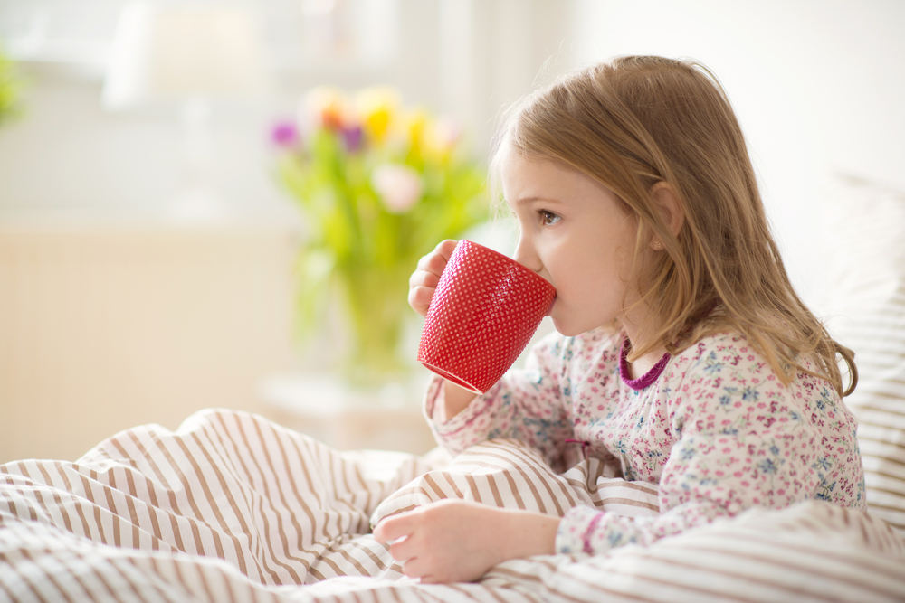 young girl in bed with mug of warm drink