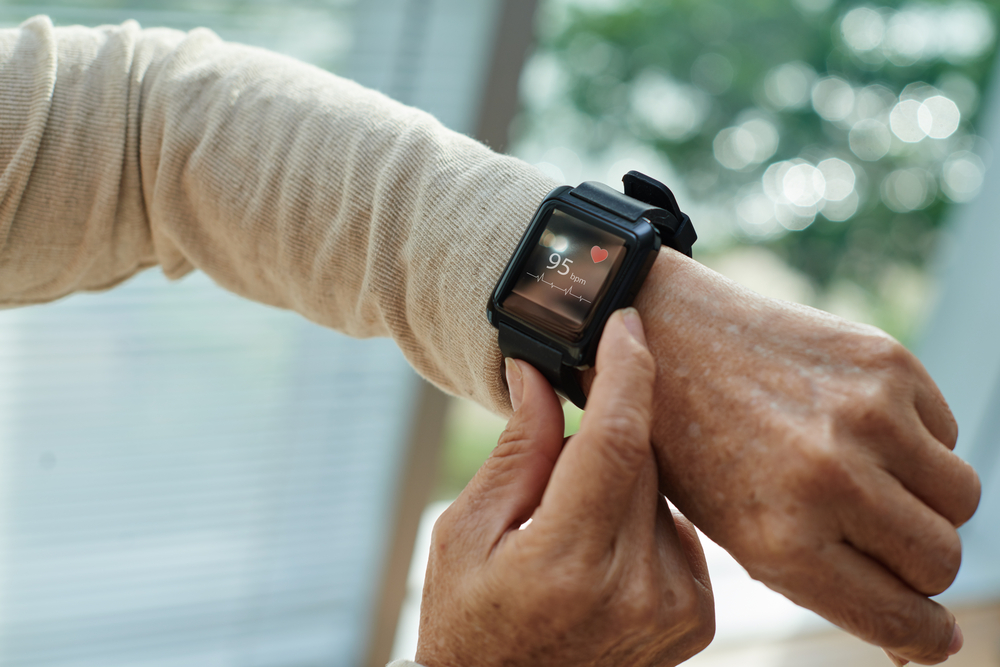 older person checking heart rate on fitness tracker