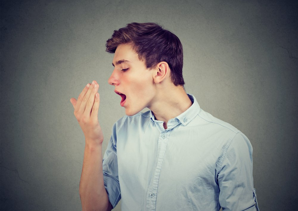 young man smelling his breath against his hand