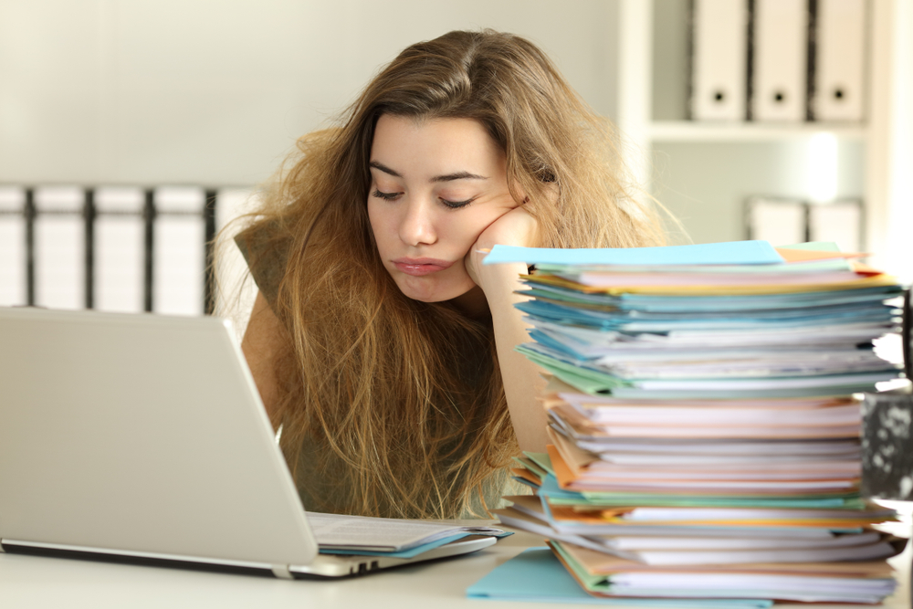 frustrated young woman in front of computer with stack of papers