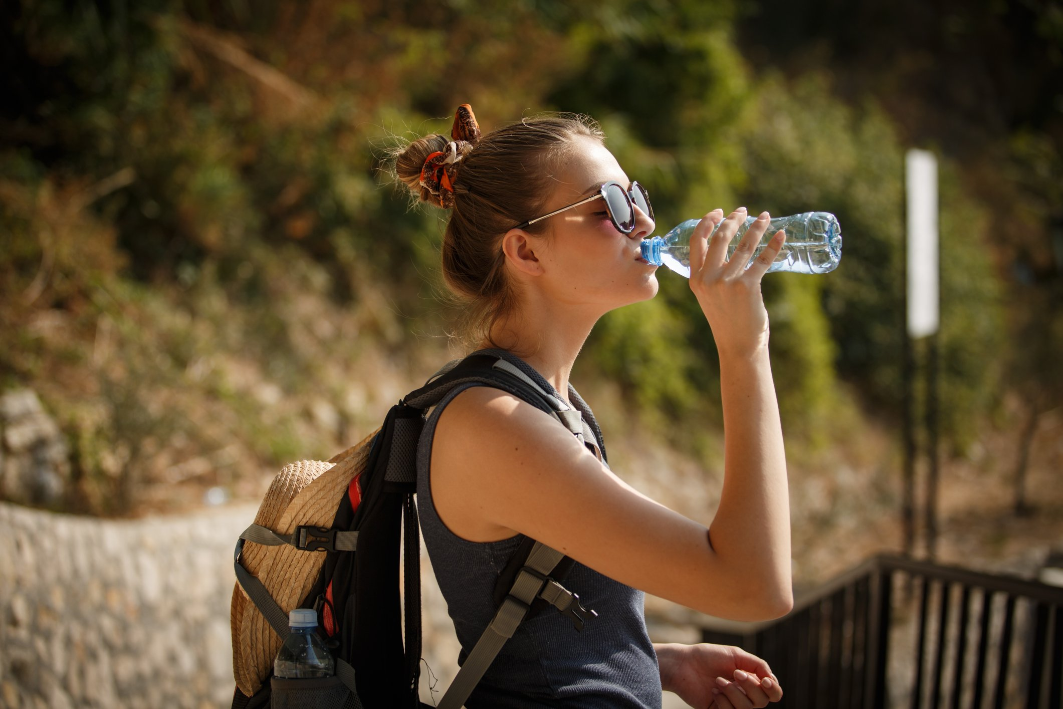 Side view of a young woman with a backpack drinking water from a plastic bottle outdoors.