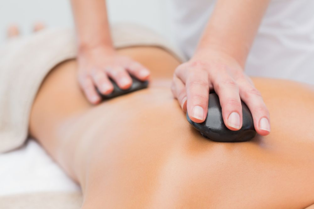 cropped image of a hot stone massage on client's back