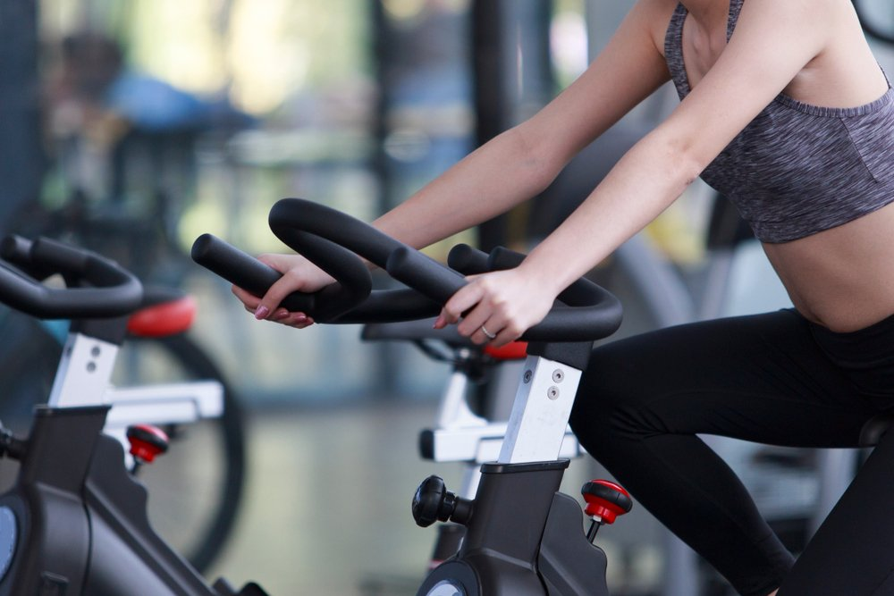 young woman on stationary bike at the gym