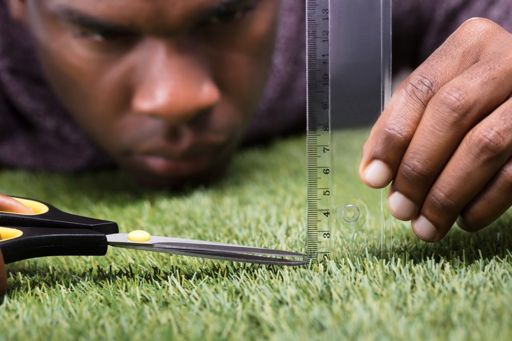 man is measuring grass and trimming with scissors; obsessive-compulsive concept
