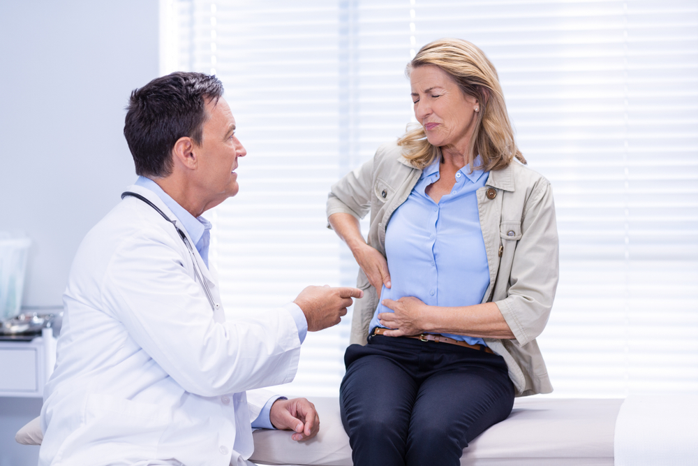 female patient showing side pain to doctor in clinic