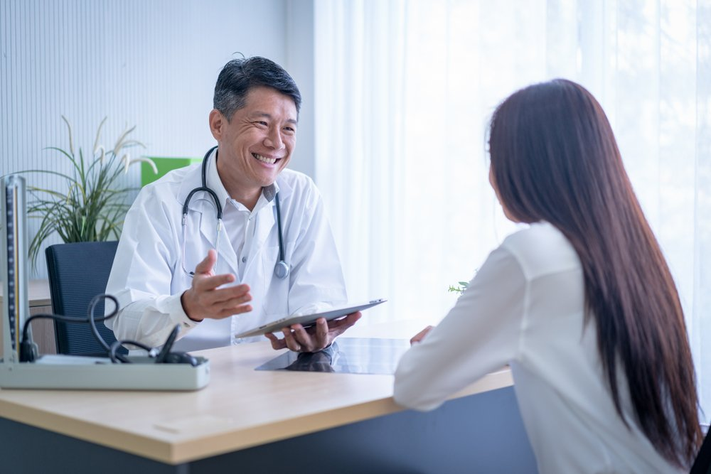 smiling male doctor talking to female patient