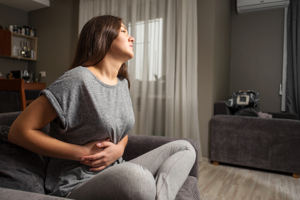 woman holding her stomach looking in pain