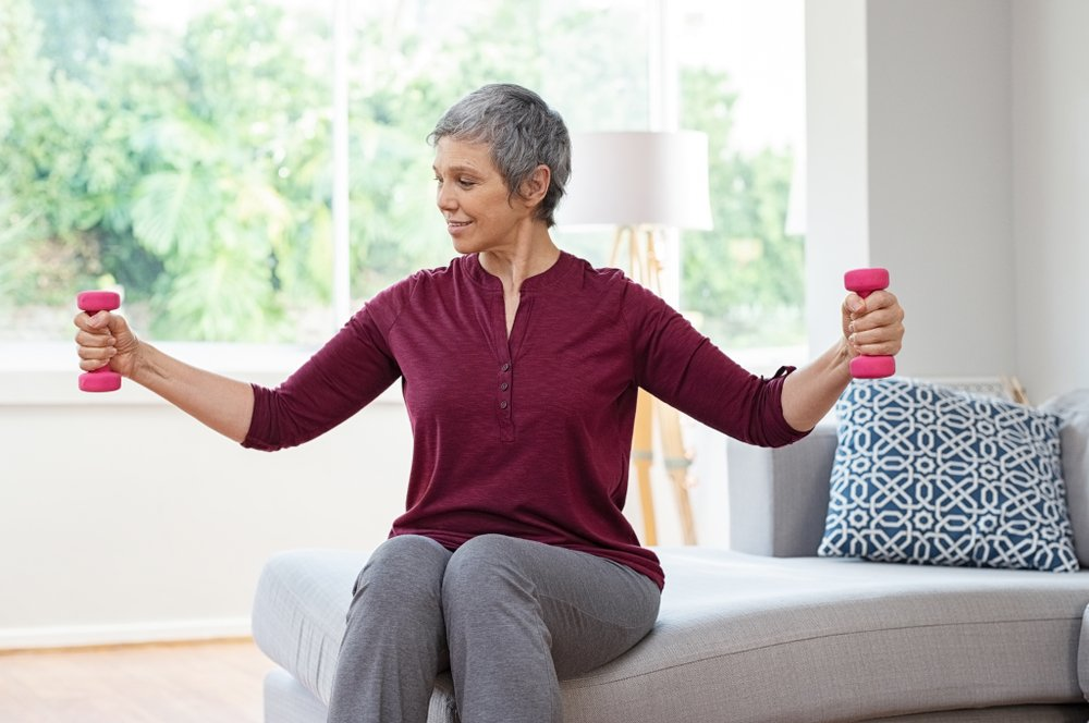 older woman lifting light hand weights