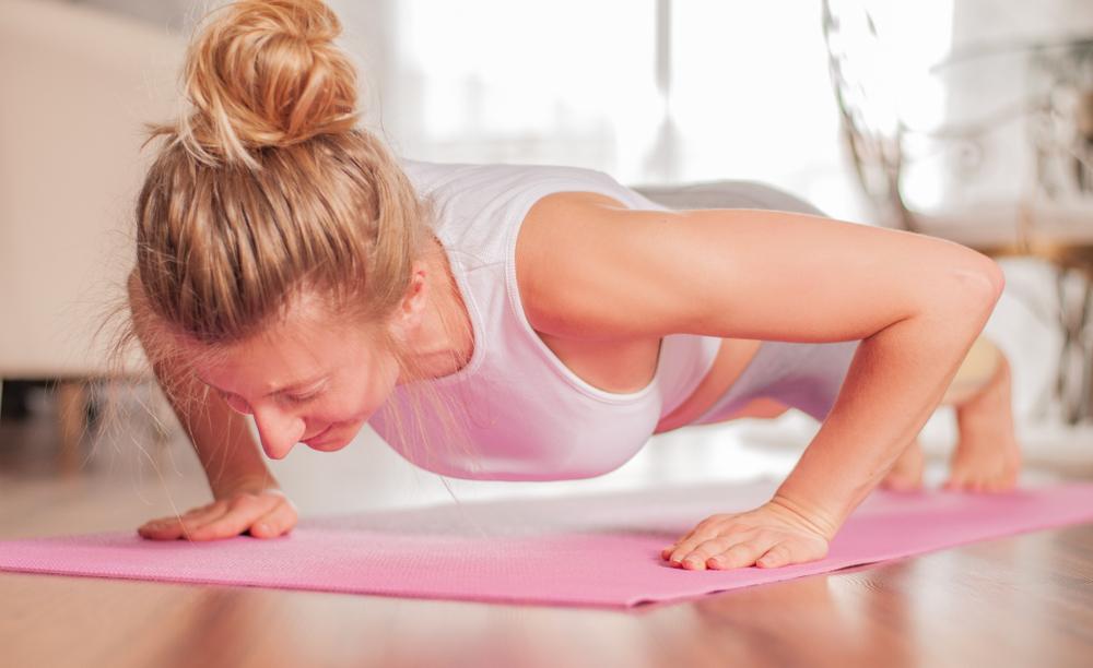 a woman doing pushups on a yoga mat