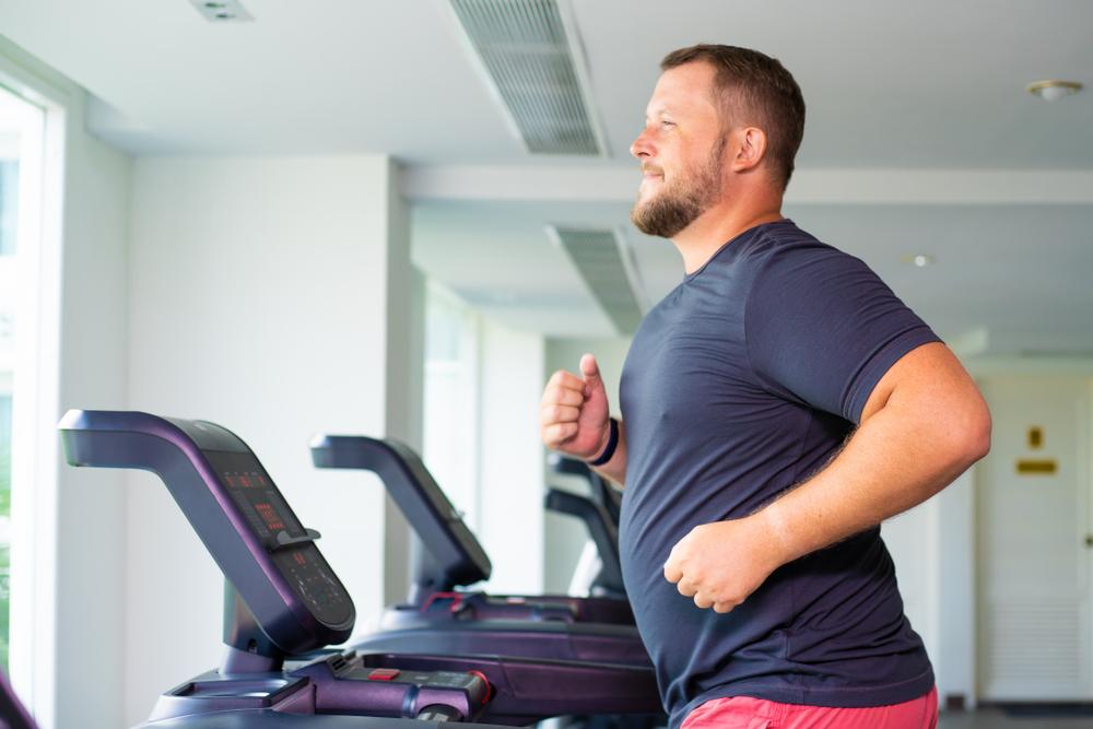 overweight man running on a treadmill