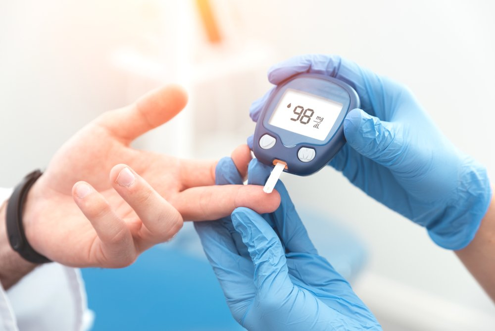 doctor checking diabetic patient's blood sugar level