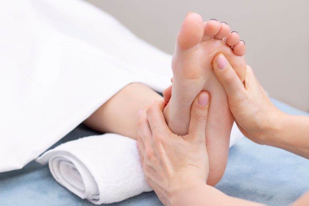 cropped image of reflexology massage on client's foot