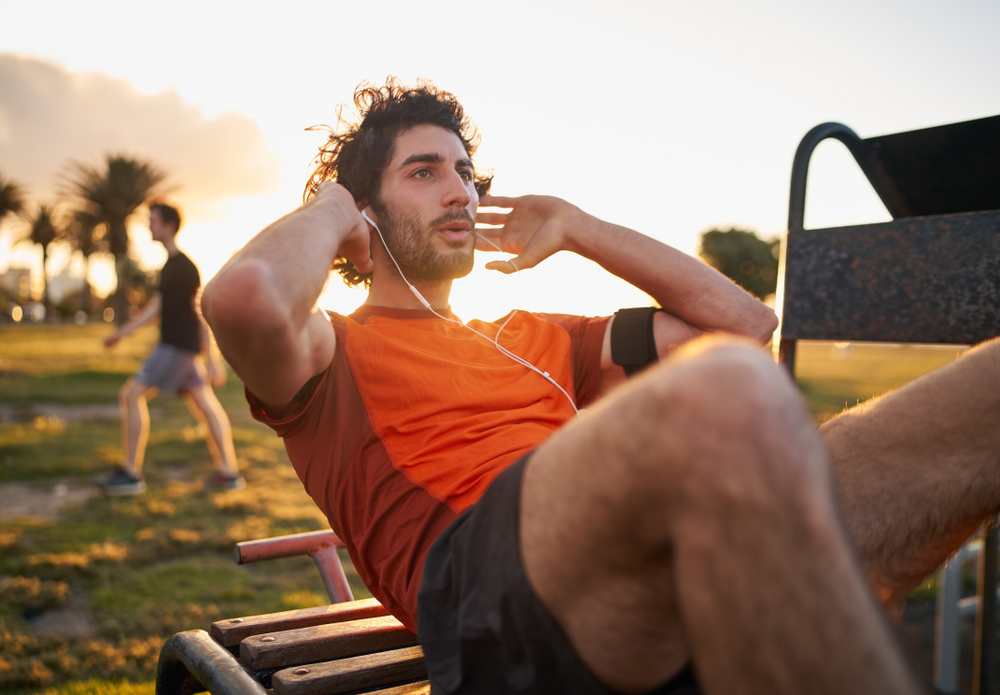 man doing crunches exercise in the park