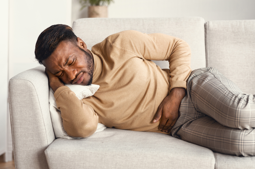 man on couch holding his stomach and in pain