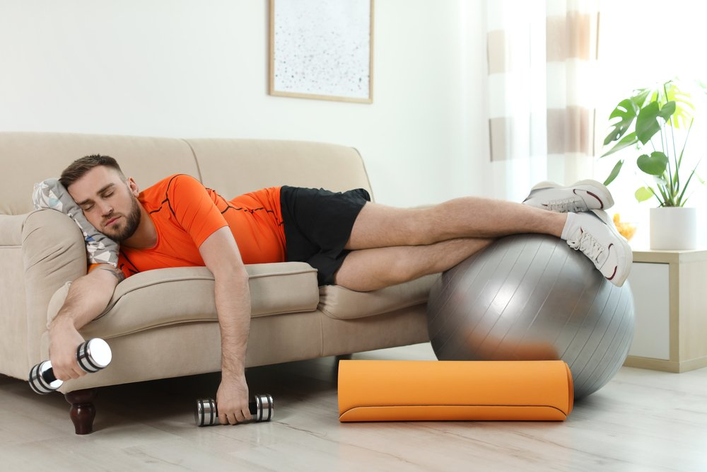 man with fitness equipment sleeping on the couch