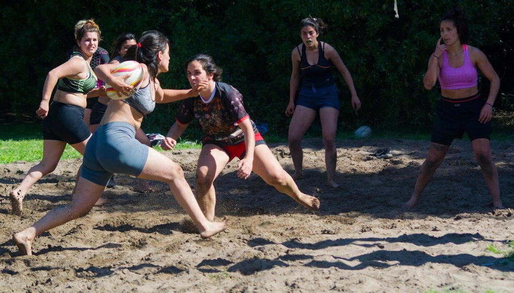 young women playing rough sport on the beach