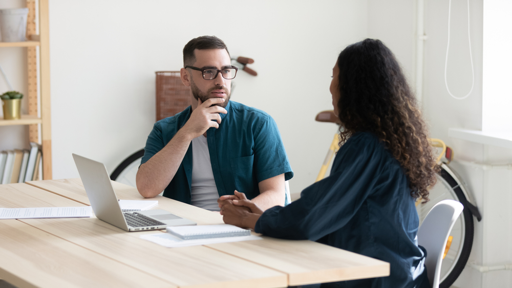 two people having a chat in a bright modern office