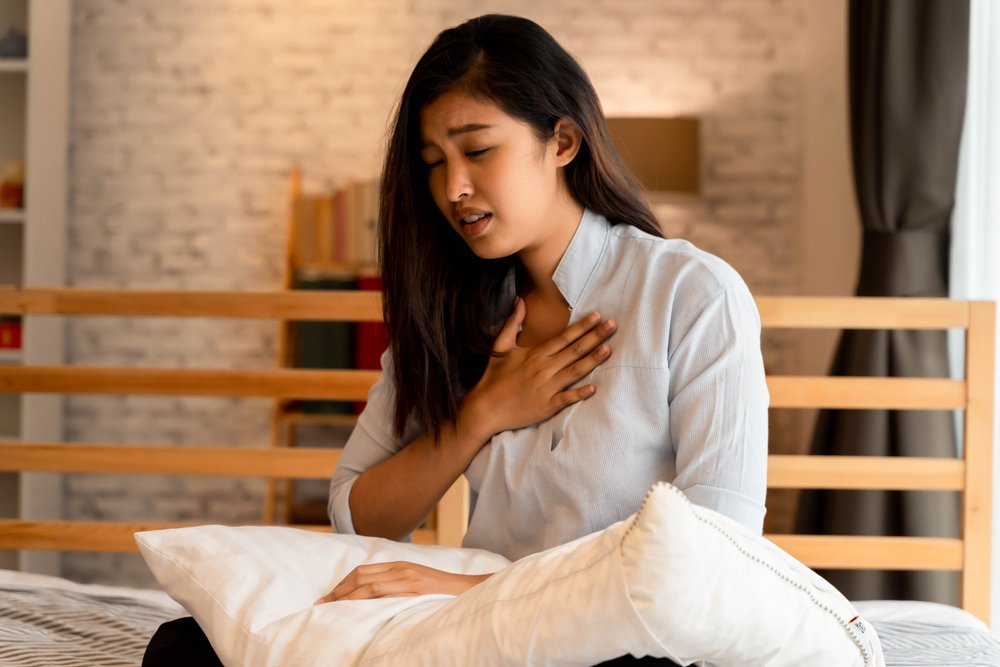 young woman in bed having trouble breathing
