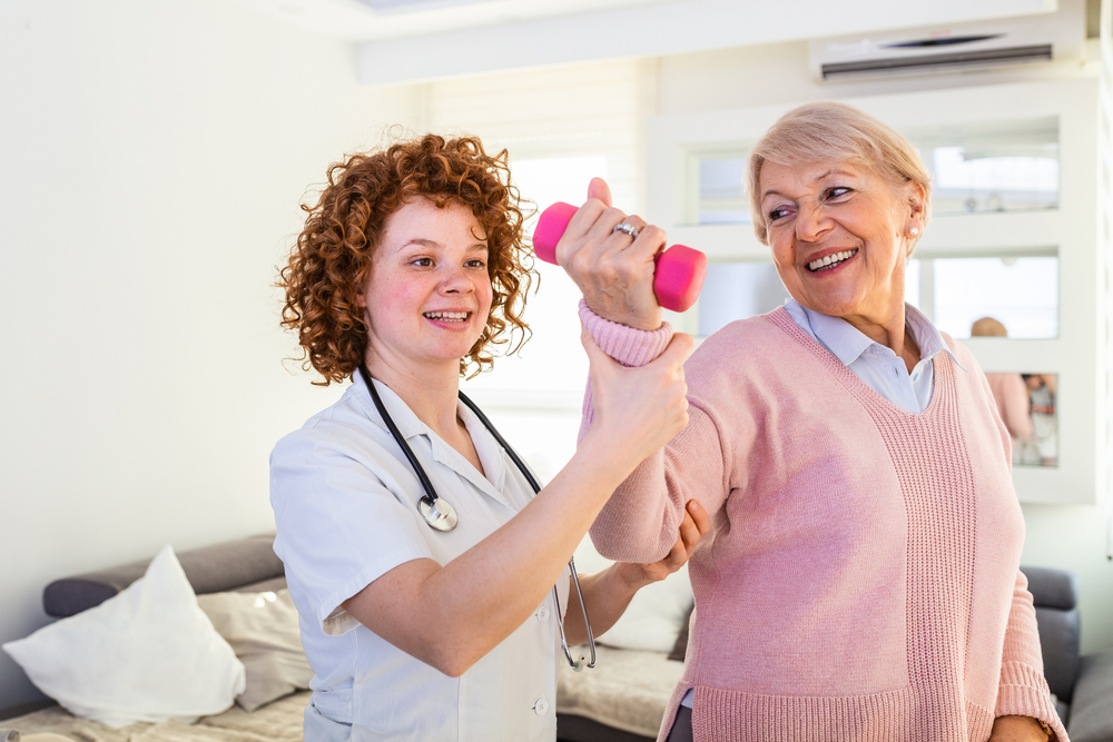 medical professional helping senior woman lift weights; stroke recovery