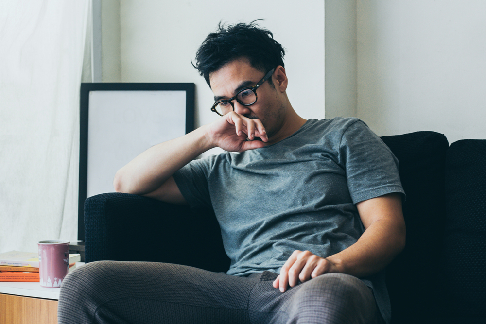 unhappy man alone on his couch