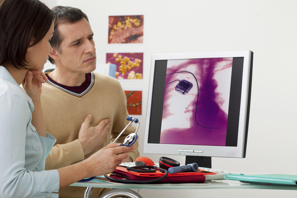 doctor explaining male patient's pacemaker and viewing x-ray