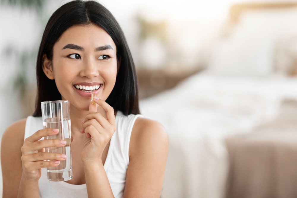 smiling woman about to take fish oil supplement with water