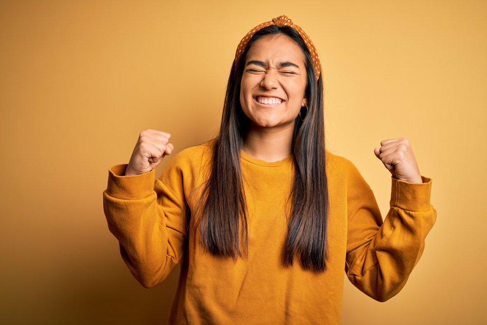 grinning, excited young woman on plain background