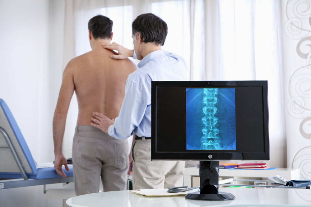 doctor inspecting male patient's spine