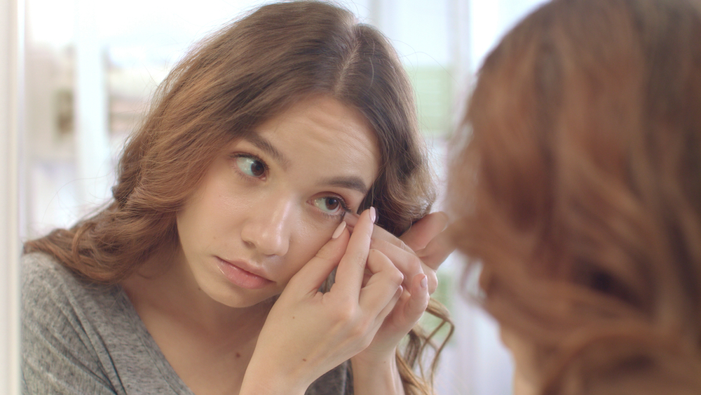 young woman removing her contact lens