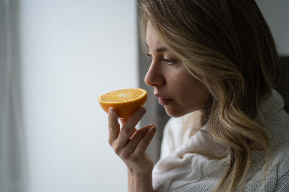 middle-aged woman smelling fruit