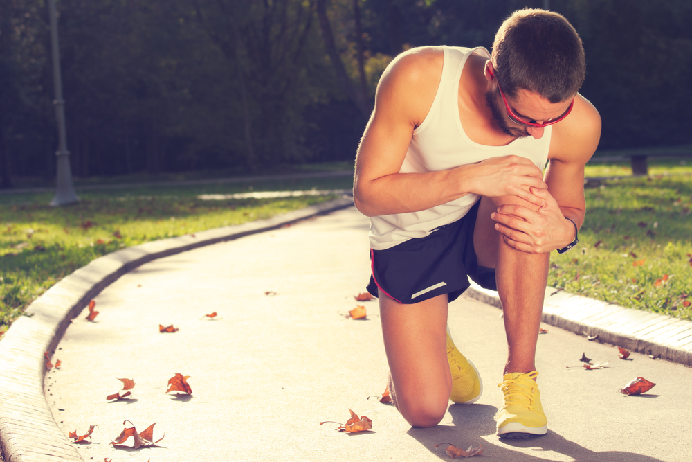 jogger holding his knee in pain