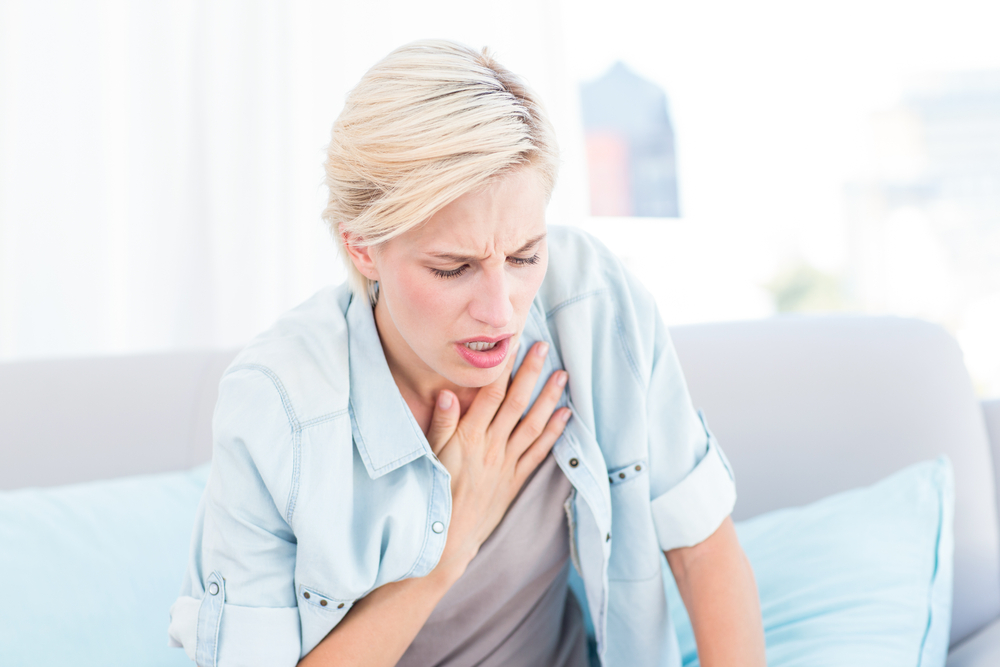 woman sitting on couch having trouble breathing