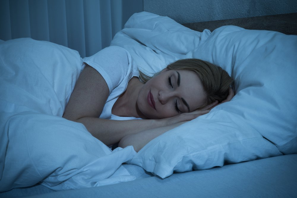smiling woman sleeping in bed