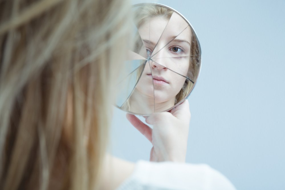 young woman looking into cracked hand mirror
