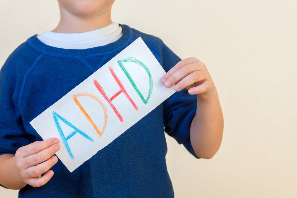 little boy holding ADHD sign