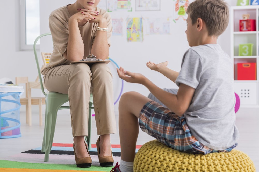 psychologist listening to young boy patient