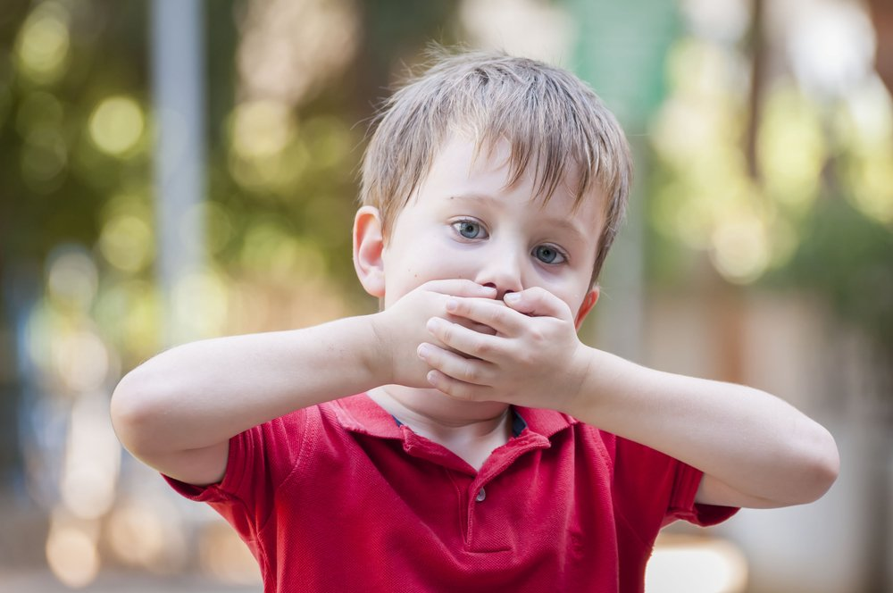 little boy with sore mouth covering his face
