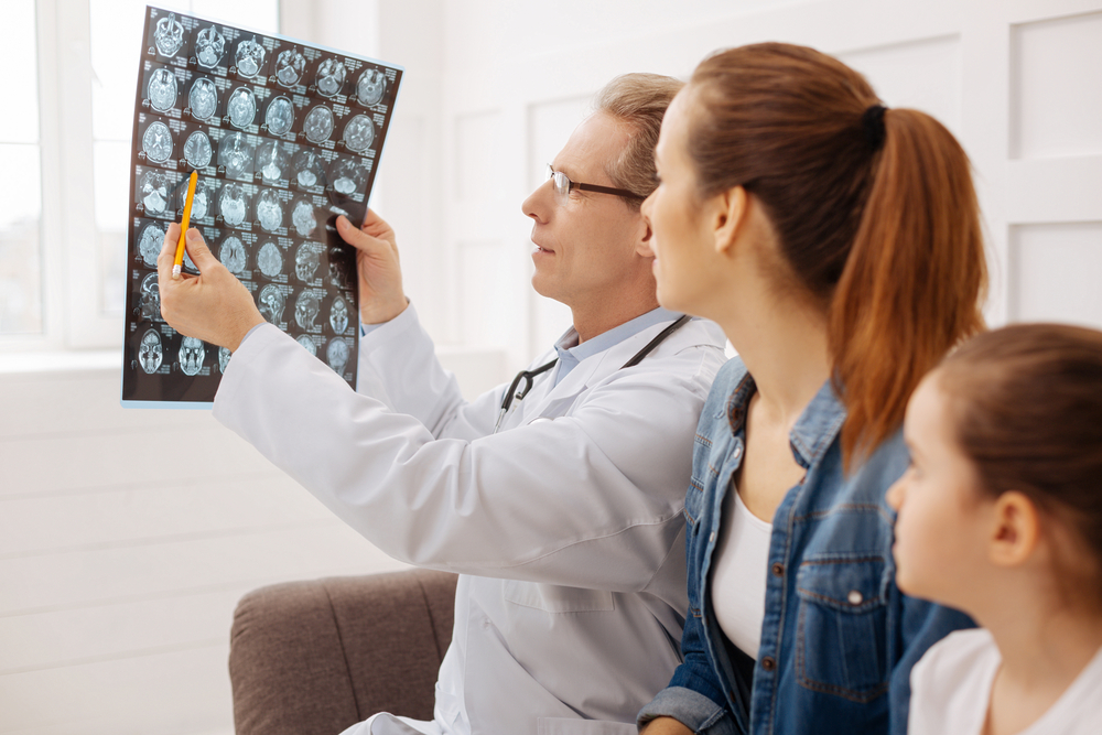 doctor showing brain scan to little girl and mother
