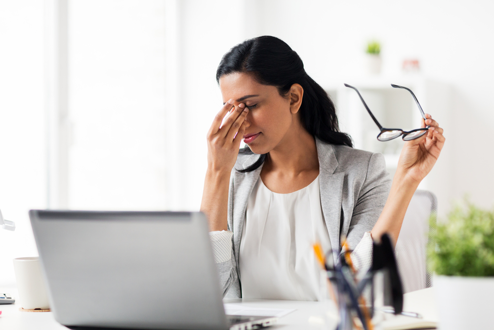 business woman at computer removing glasses to rub her eyes