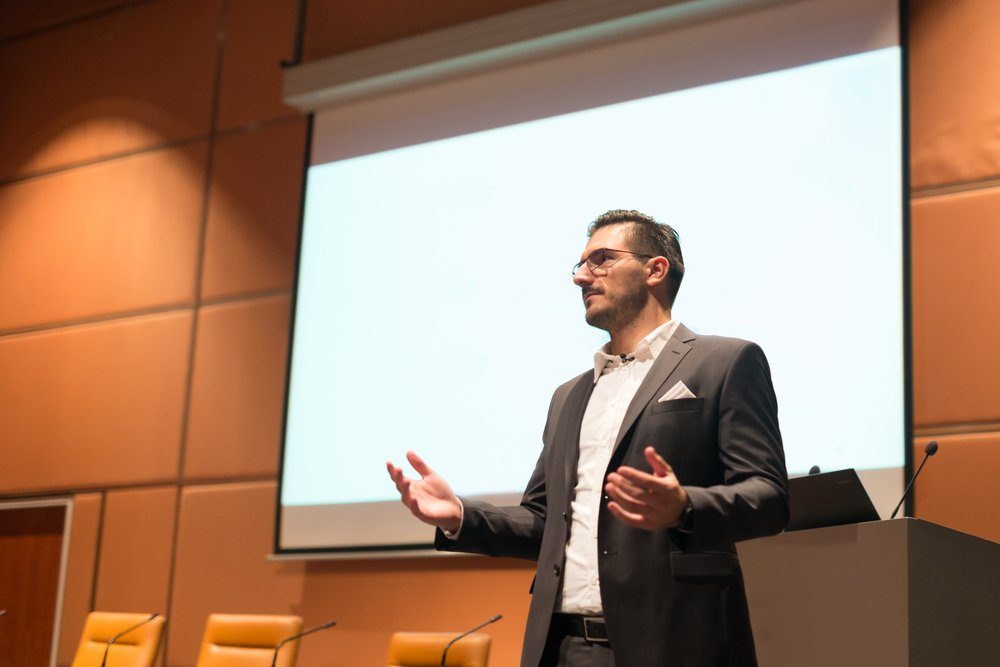 man in front of a podium, giving a presentation